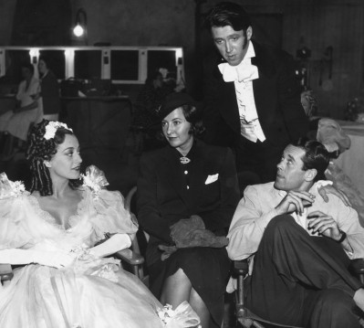 Joan Crawford, Barbara Stanwyck, Jimmy Stewart (standing) and Henry Fonda on the set of The Gorgeous Hussy