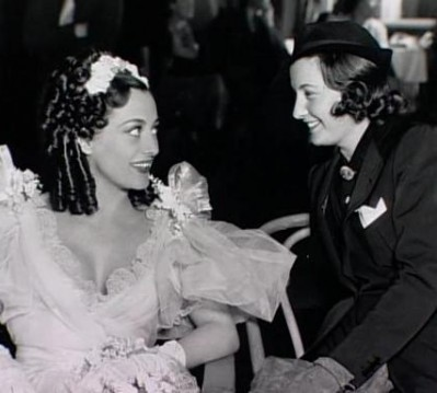 With Joan Crawford in 'Peggy Eaton' costume on the set of Metro's, The Gorgeous Hussy, directed by Clarence Brown.